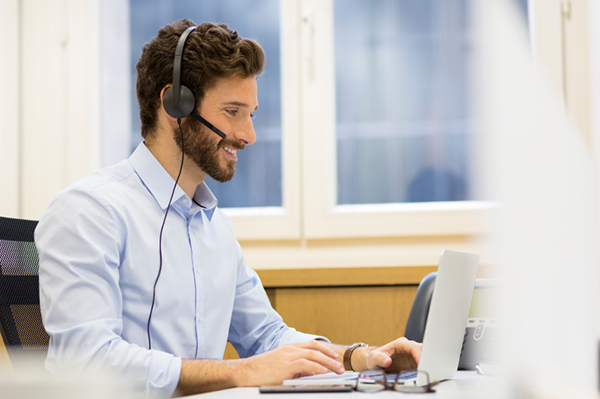 Happy Businessman in the office on the phone, headset, Skype