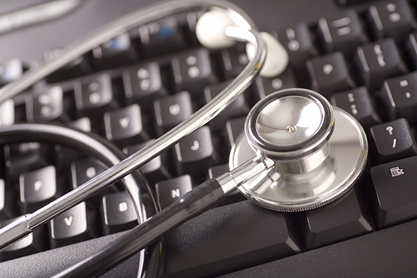 Stethoscope on a Computer Keyboard. Blue-toned.