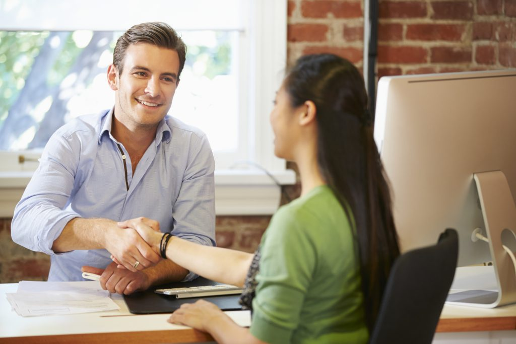 Businessman Interviewing Female Job Applicant In Office Shaking Hands