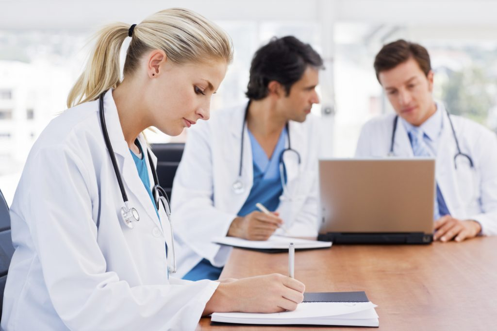 Busy young female doctor with colleagues around a table