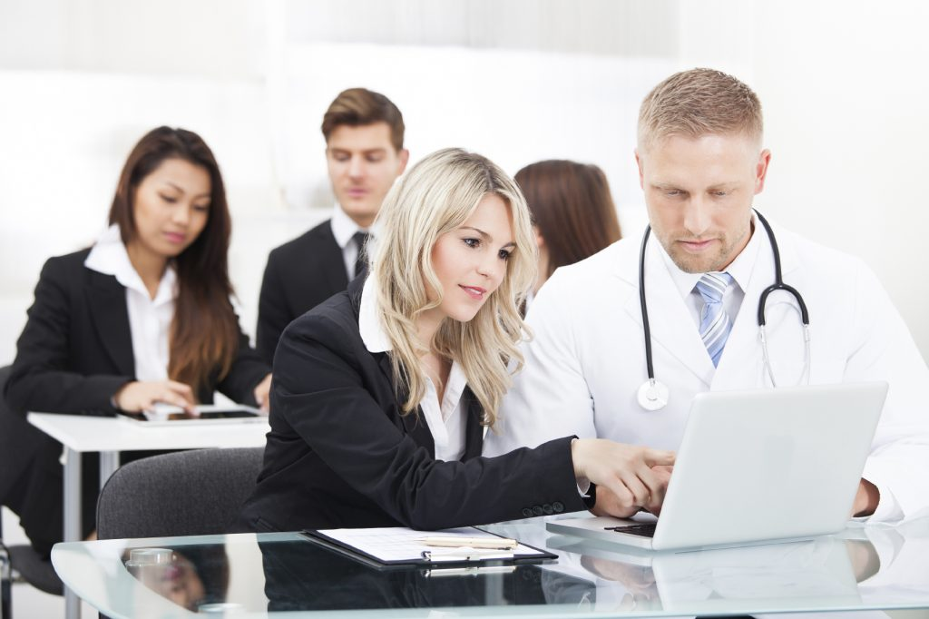 Portrait of male doctor and businesswoman with laptop sitting at desk in office